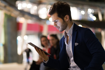 Young manager using a digital tablet outdoor in a modern city at night