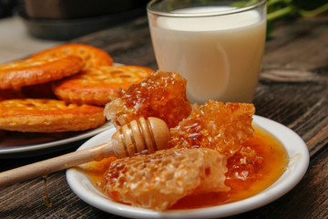 Honey with honeycomb in a white ceramic plate, cookies with jam and cup of milk on rustic wooden table