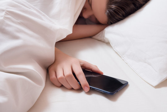 Young girl under the blanket with smart phone in the hand