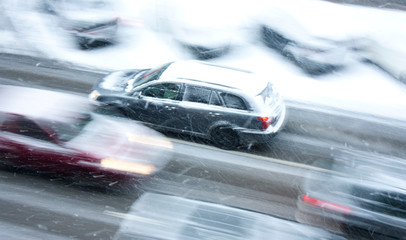 Driving cars on the snowy city street in motion blur