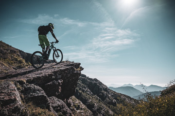 mountain biker riding up a large rock deep in the alps with sun and mountain layers behind Fototapete