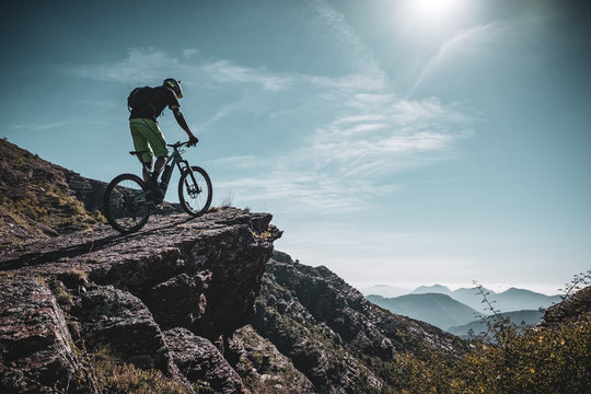 mountain biker riding up a large rock deep in the alps with sun and mountain layers behind