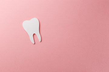White tooth on pink background with copy space. Oral dental hygiene. Teeth whitening. Dental health concept. Oral care, teeth restoration. Dentist day concept. Flat lay. Top view. Pastel colors