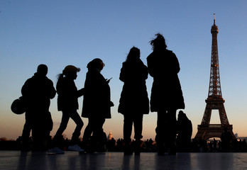 People stand at the Trocadero square near the Eiffel Tower in Paris