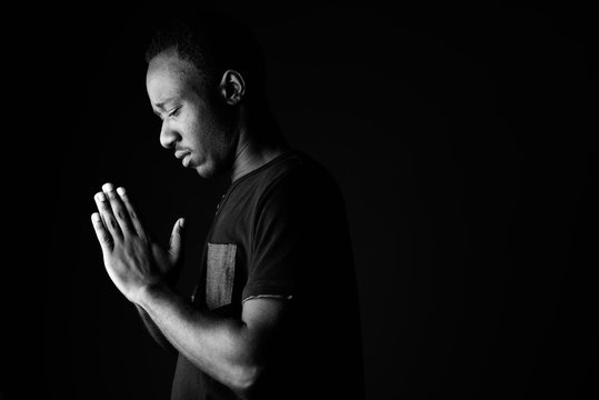 Sad young African man praying in black and white