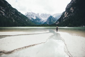 Woman standing in a lake surrounded my mountains