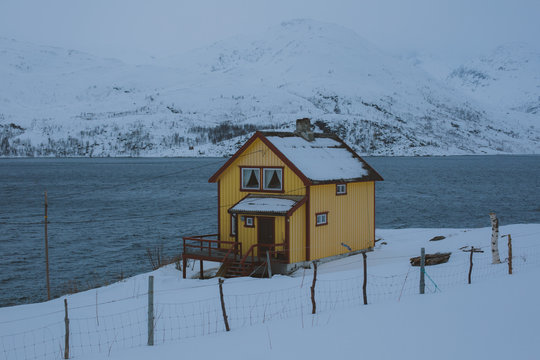 A yellow house by a river and snow covered fields