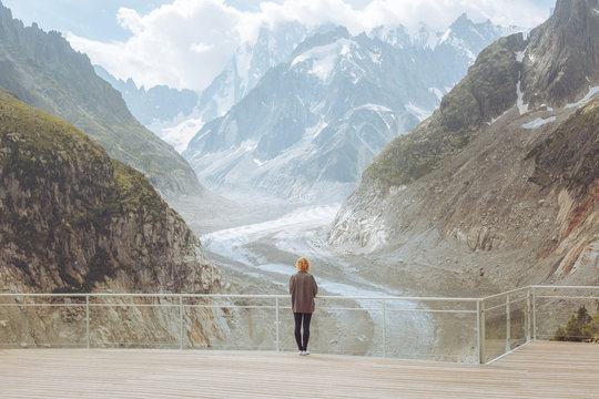 Rear view of woman standing on bridge against mountains