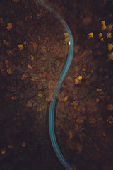 Aerial of a car driving on a curved road