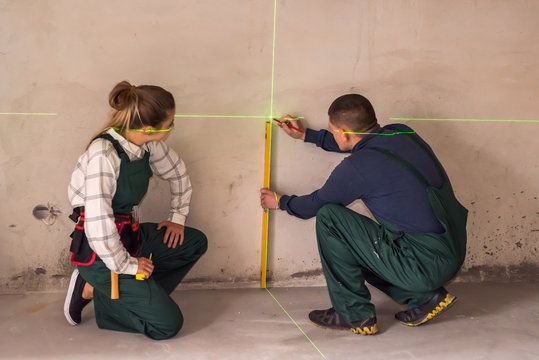 Workers measuring walls with laser level tool