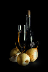 still life; bottle of wine, whole pears and half on a dark background