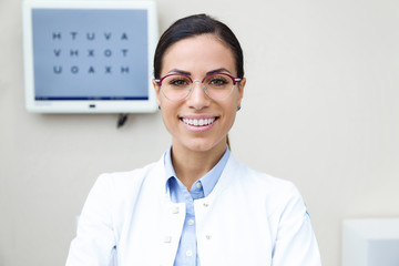Pretty young woman ophthalmologist smiling while looking at camera in the consultation.