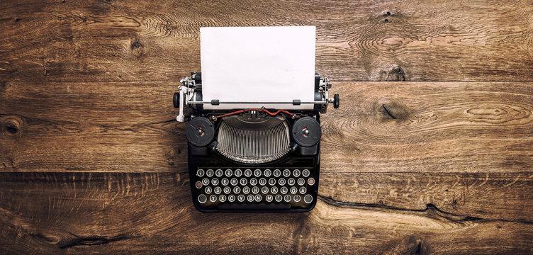 Vintage typewriter paper wooden background toned
