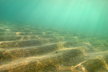 """Underwater photo, small sand """"dunes"""" shot diagonally so in this perspective they form stairs, sun rays coming from sea surface. Abstract marine background."""