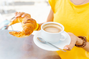 Happy woman in yellow having breakfast with croissants and coffee in outdoor cafe