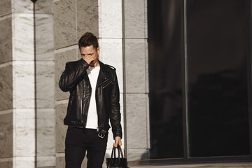 Picture of stylish young male dressed in trendy clothes carrying black leather bag rubbing his eyes, feeling sleepy or frustrated because of shopping with his girlfriend, posing in urban surroundings