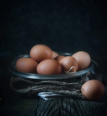 clean eggs in a metal bowl on a dark background. . Dark and moody picture. Low key. Rustic.  Close up, selective focus. Copy space