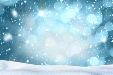 Falling snow with white snow on the ground at night and freezing blue tone bokeh of lights in background. Copy space.