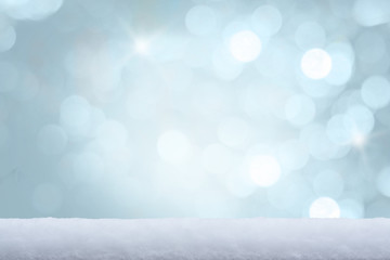 White snow on the ground and freezing blue tone bokeh of lights in background. Copy space.