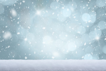 Falling snow with white snow on the ground and freezing blue tone bokeh of lights in background. Copy space.
