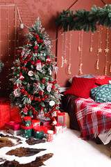 Christmas, New year interior with red brick wall background, decorated Christmas tree with garlands and balls, dark box and horse figure