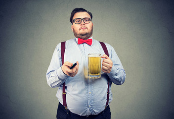 Chubby man with beer and TV remote