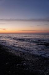 Sonnenuntergang am Strand mit Wellen und Sand an der Ostsee nahe Warnemünde im Urlaub