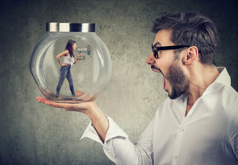 Frustrated business man holding a glass jar with an angry screaming woman trapped in it