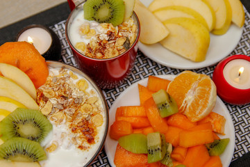 Healthy food, various seeds, integral cereals and dried fruits in yogurt. Fresh fruit, apple, orange, kiwi and persimmon. Wooden table with modern black and white mat and candle light.