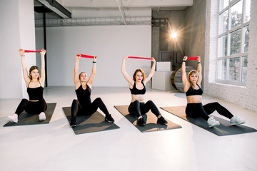 Group of young cheerful women doing exercises with fitness rubber tape