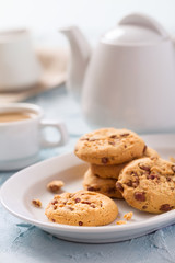 Chocolate chips cookies with cup of coffee with milk on pastel blue background.