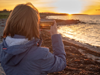 Woman taking picture on her smart phone of beautiful sunset over ocean, the phone is in focus.