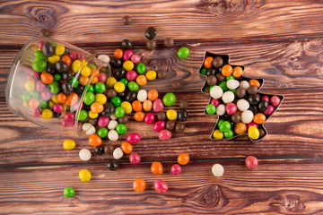Variety of multicolored dragee sweets dropped out of the glass can laying on brown wooden background Fototapete