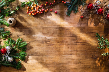 Empty wooden table framed with Christmas decorations