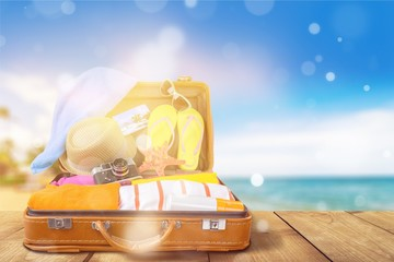 Retro suitcase with travel objects on wooden desk in beach