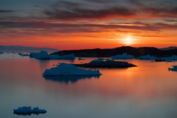 Sunset time on the arctic ocean with icebergs
