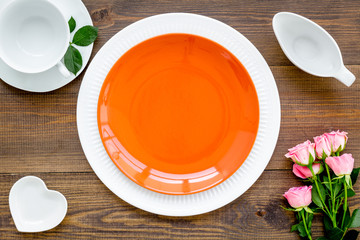 Simple color table setting for celebration with roses, orange plates and heart-shaped saucers on wooden table background top view mock up