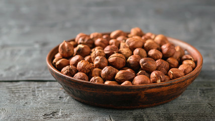 A clay bowl full of walnut kernels on a black rustic table. Vegetarian cuisine.