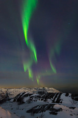 Beautiful northern lights, aurora in the night sky over the snow-covered hills.