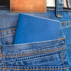 Closeup blue passport in man's jeans pocket. Ready for traveling and vacations.