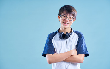 Portrait of Asian teenage smiling boy in studio with light blue background . Music headphone concept .