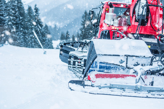 Red ratrac snowcat at work on on the ski slope