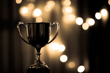 Gold Trophy competition in the dark on the abstract blurred light background with copy space, Spectacular success Concept