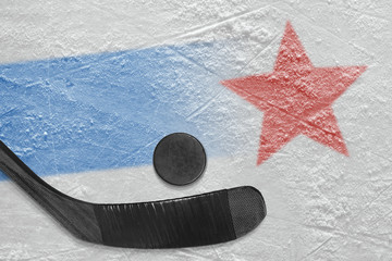 An image of a blue line with a red star on ice and a stick with a puck