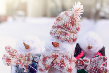 snowmen in warm clothes outdoors in winter / fun weekend in the fresh air