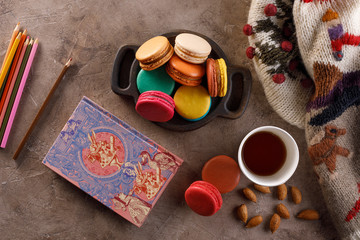A cup of coffee with macarons and a warm sweater. The concept of autumn or winter. Flat lay.