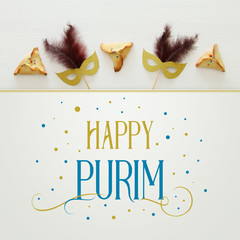 Purim celebration concept (jewish carnival holiday) over white wooden background. Top view.