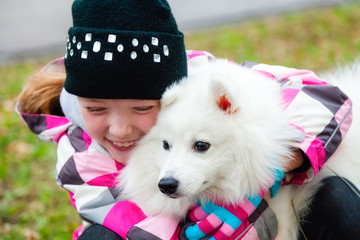 Girl is hugging her dog on the street