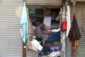 Man reads the Koran at a fabrics shop, early morning in Karachi