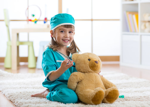 Happy child little doctor girl examines teddy bear in nursery room at home.